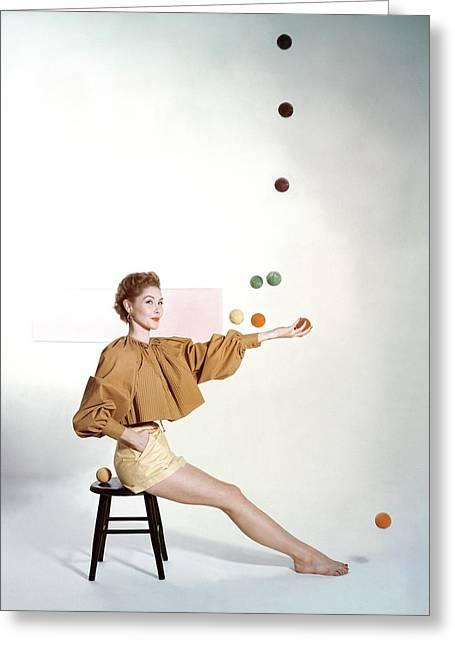 A Model Sitting On A Stool Juggling Greeting Card by John Rawlings