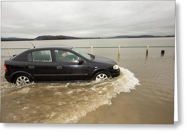 A Motorist Travels Through Flood Waters Greeting Card by Ashley Cooper