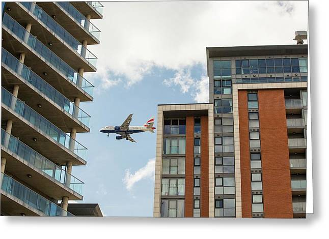 A Plane Flying Past Apartment Blocks Greeting Card by Ashley Cooper