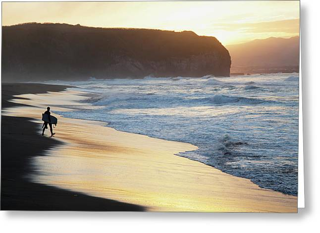 A Surfer Walks To The Water At Sunrise Greeting Card by Carl Bruemmer