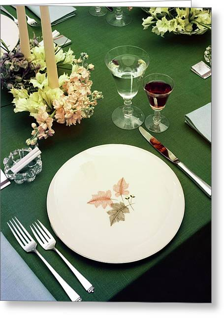 A Table Setting On A Green Tablecloth Greeting Card