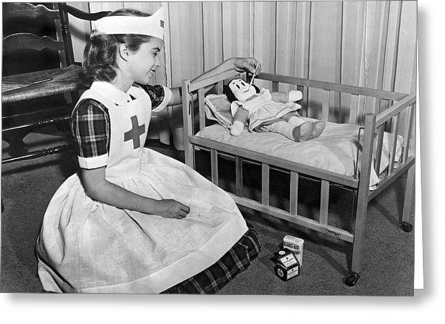 A Young Girl Plays Nurse To Her Little Lulu Doll. Greeting Card by Underwood Archives