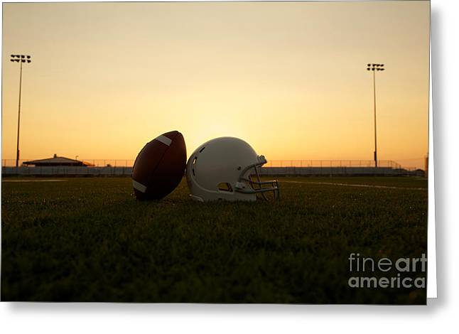 American Football And Helmet On The Field At Sunset Greeting Card