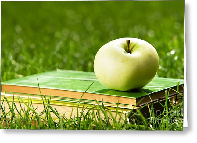 Apple On Pile Of Books On Grass Greeting Card by Michal Bednarek