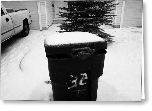 bag sticking out of litter waste bin covered in snow outside house in Saskatoon Saskatchewan Canada Greeting Card