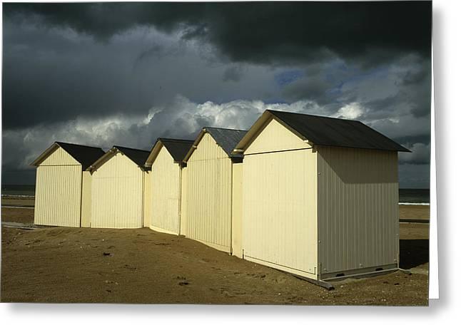 Beach Huts Under A Stormy Sky In Normandy. France. Europe Greeting Card by Bernard Jaubert
