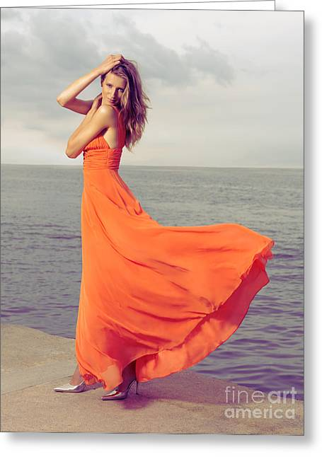 Beautiful Woman In Orange Dress On Sea Shore Greeting Card by Oleksiy Maksymenko