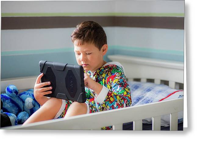 Boy Sitting In Bed Using A Digital Tablet Greeting Card by Samuel Ashfield
