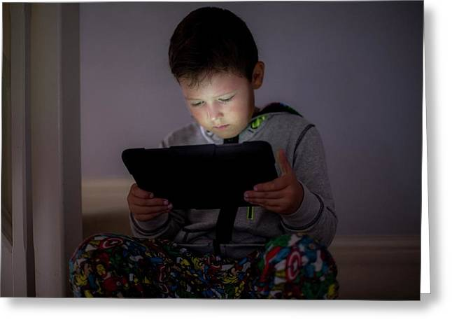 Boy Using A Digital Tablet In The Dark Greeting Card by Samuel Ashfield