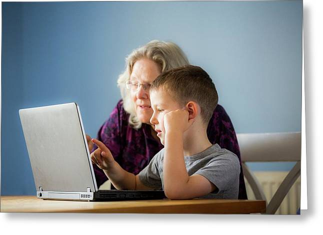 Boy Using Laptop With Grandmother Greeting Card by Samuel Ashfield