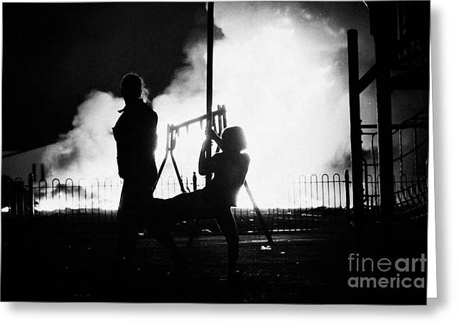 children play in playground at 11th night bonfire in Monkstown fire northern ireland Greeting Card by Joe Fox
