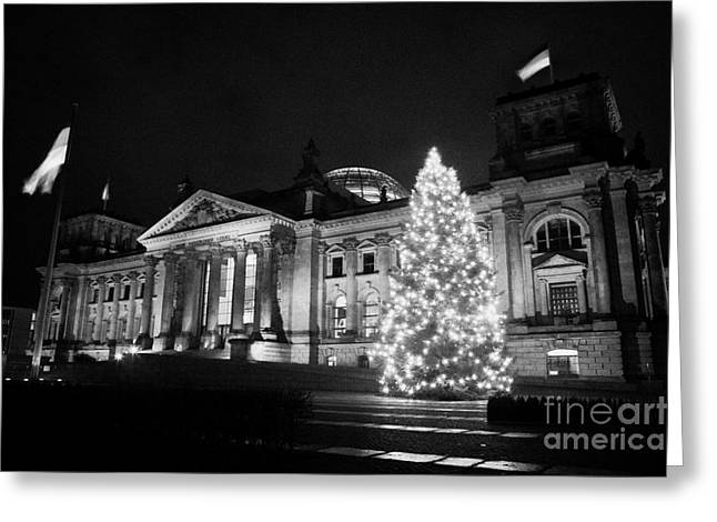 christmas tree and german flag flying fluttering on flagpole outside reichstag building Berlin Germany Greeting Card by Joe Fox