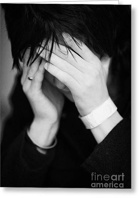 Close Up Of Young Dark Haired Teenage Man Sitting With His Head In His Hands Hiding His Face Staring Greeting Card