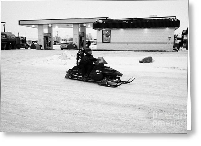 couple on a snowmobile leaving a gas station Kamsack Saskatchewan Canada Greeting Card