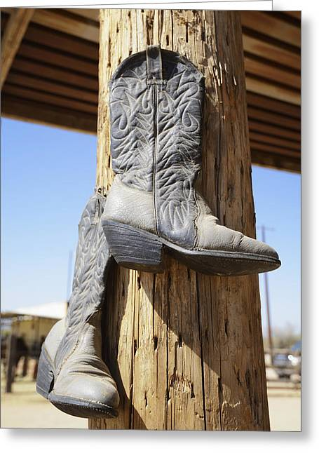 Cowboy Boots Hanging From A Post At A Greeting Card by Peter Carroll