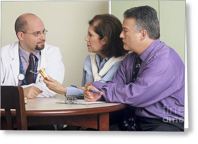 Doctor And Couple Seated Around A Table Greeting Card by National Institutes of Health