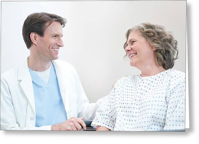 Doctor Smiling At Woman Patient Greeting Card by Science Photo Library
