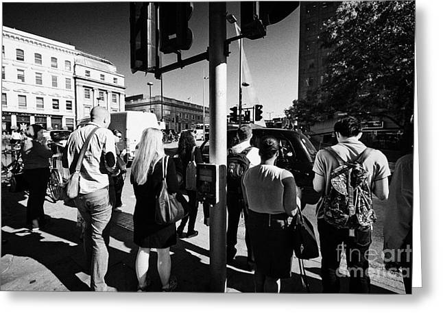 early morning commuters waiting to cross the road pedestrian crossing London England UK Greeting Card