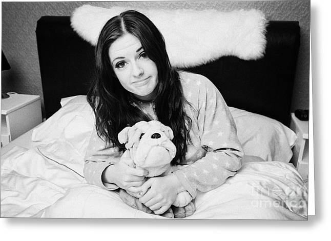 Early Twenties Woman Holding Cuddly Dog Soft Toy In Bed In A Bedroom Greeting Card by Joe Fox