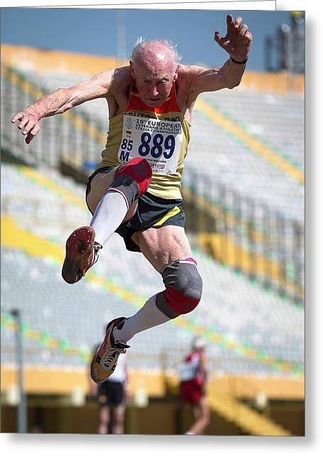 Elderly Male Athlete Jumping Mid-air Greeting Card by Alex Rotas