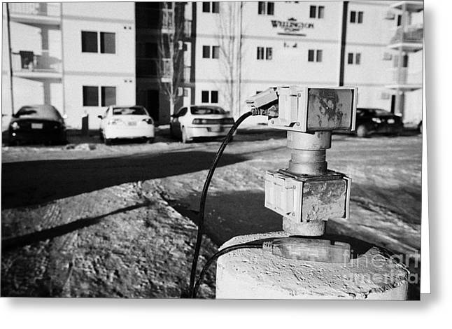 electric power connection for engine block heaters in residential parking bay outside homes in Saska Greeting Card by Joe Fox
