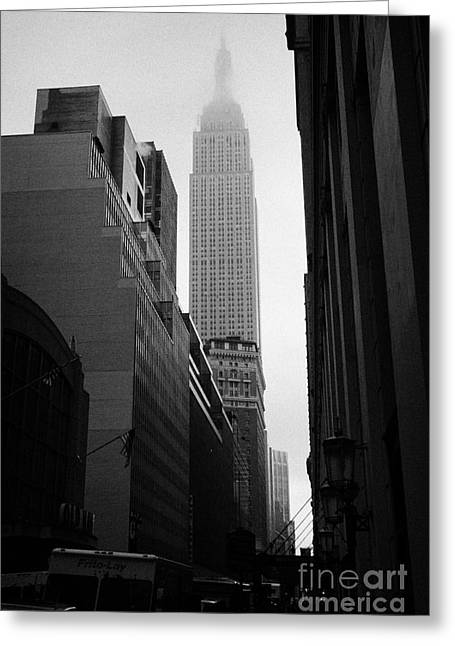 empire state building shrouded in mist in amongst dark cold buildings on 33rd Street new york city Greeting Card