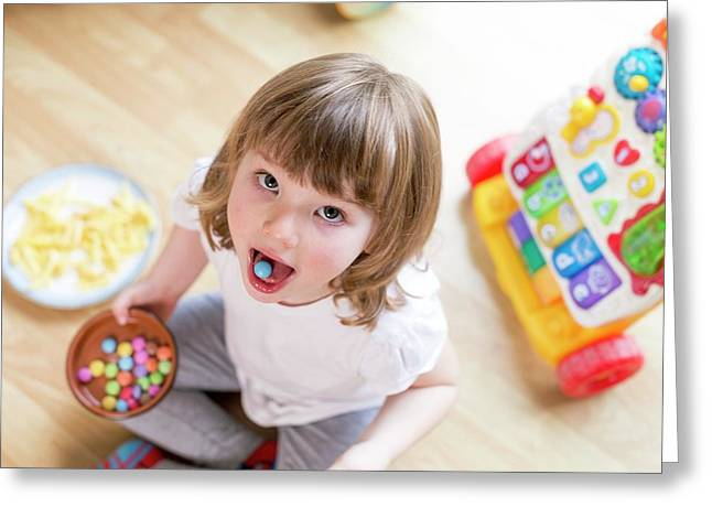 Girl Sitting On Floor With Bowl Of Sweets Greeting Card by Aberration Films Ltd