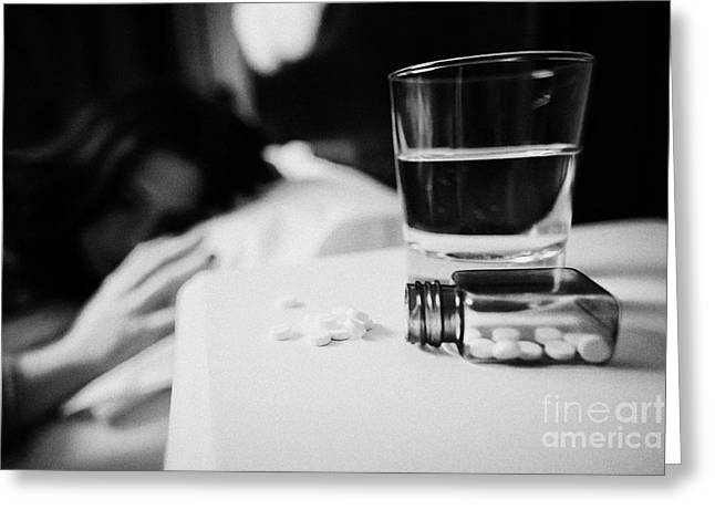 Glass Of Water And Bottles Of Sleeping Pills On Bedside Table Of Early Twenties Woman In Bed In A Be Greeting Card by Joe Fox
