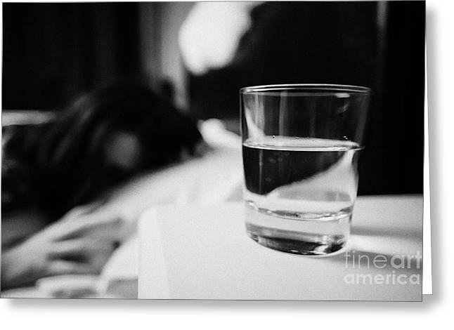 Glass Of Water On Bedside Table Of Early Twenties Woman In Bed In A Bedroom Greeting Card by Joe Fox