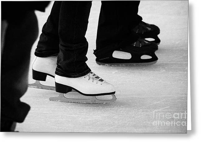 legs and feet of people ice skating on an outdoor rink for christmas Berlin Germany Greeting Card