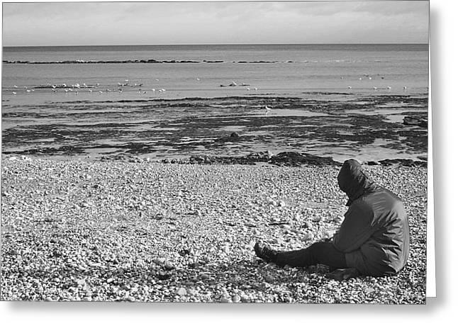 Lone Man Sitting On Pebble Beach Greeting Card by Natalie Kinnear