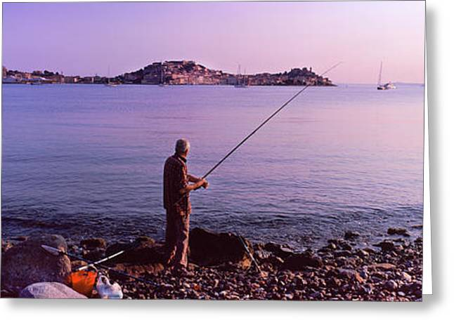 Man Fishing At The Coast, Portoferraio Greeting Card by Panoramic Images