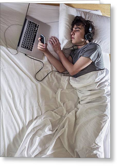 Man In Bed With Laptop And Phone Greeting Card by Mauro Fermariello