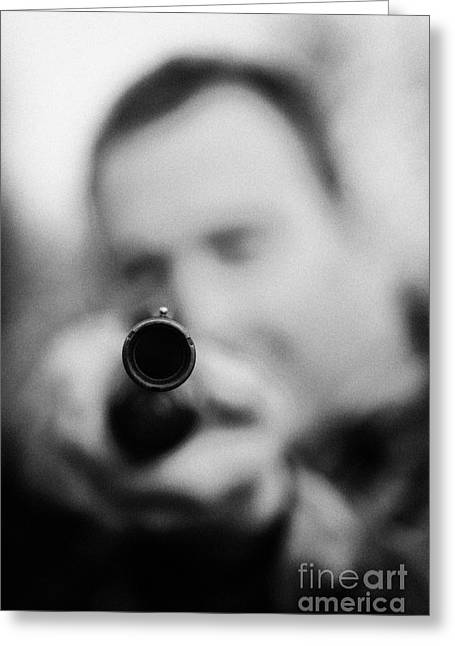 Man In Camouflage Clothes Takes Aim At Camera With Shotgun Close Up  On December Shooting Day Greeting Card