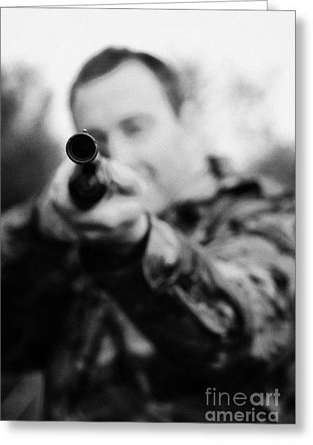 Man In Camouflage Clothes Takes Aim At Camera With Shotgun On December Shooting Day Greeting Card
