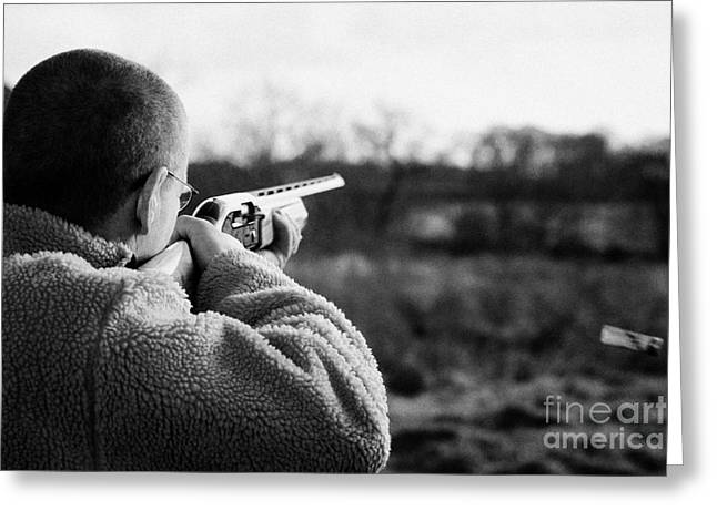 Man In Fleece Jacket Firing Shotgun Into Field With Cartridge Ejecting On December Shooting Day Greeting Card