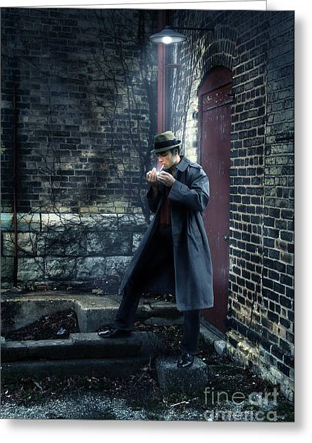 Man In Trenchcoat Lighting A Cigarette Greeting Card by Jill Battaglia