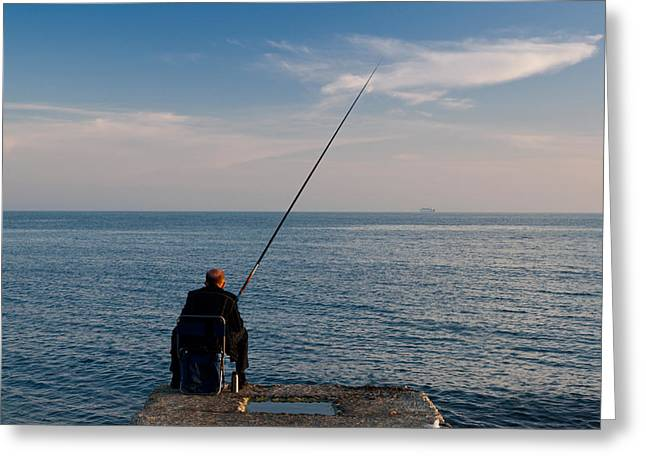 Man Pier Fishing, Lighthouse Beach Greeting Card by Panoramic Images