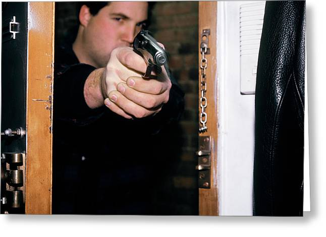 Man Pointing Gun Through Doorway Greeting Card