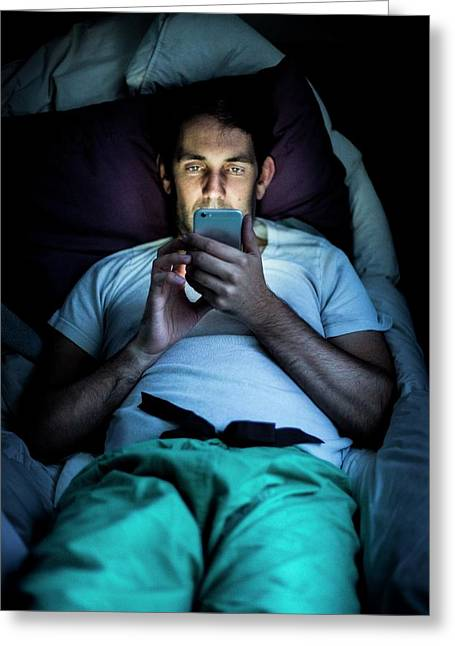 Man Using Smartphone In Bed Greeting Card by Samuel Ashfield