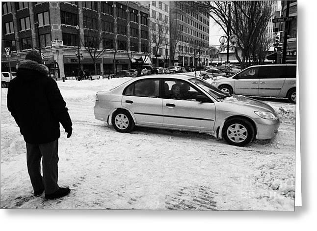 man watching car travelling along snow covered city streets in Saskatoon Saskatchewan Canada Greeting Card
