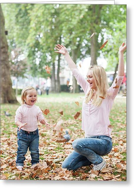Mother And Daughter Playing With Leaves Greeting Card by Ian Hooton
