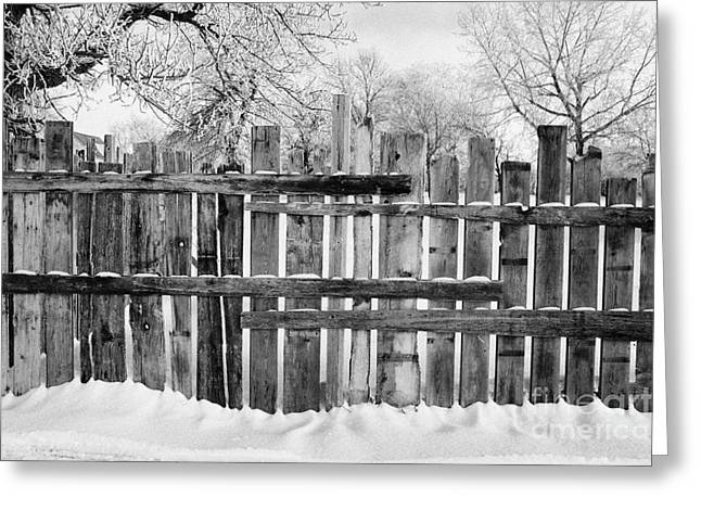 old patched up wooden fence using old bits of wood in snow Forget Saskatchewan Canada Greeting Card