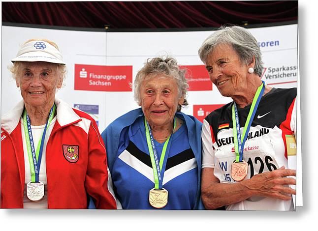 Older Female Athletes On Medals Rostrum Greeting Card