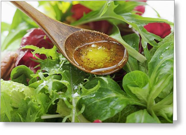 Olive Oil In Wooden Spoon Above Salad Leaves Greeting Card