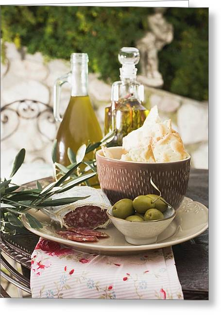 Olives, Salami, Crackers And Olive Oil On Table Out Of Doors Greeting Card