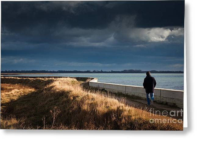 One Man Walking Alone By Sea Wall In Sunshine On Dramatic Stormy Greeting Card