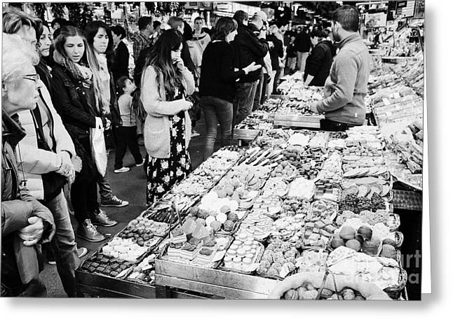 people buying chocolates on display inside the la boqueria market in Barcelona Catalonia Spain Greeting Card by Joe Fox