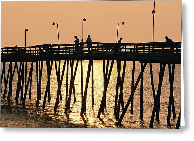 People On A Pier Are Silhouetted Greeting Card