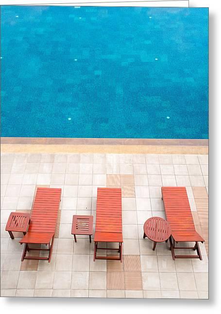 Poolside Deckchairs Alongside Blue Swimming Pool Greeting Card by Jirawat Cheepsumol